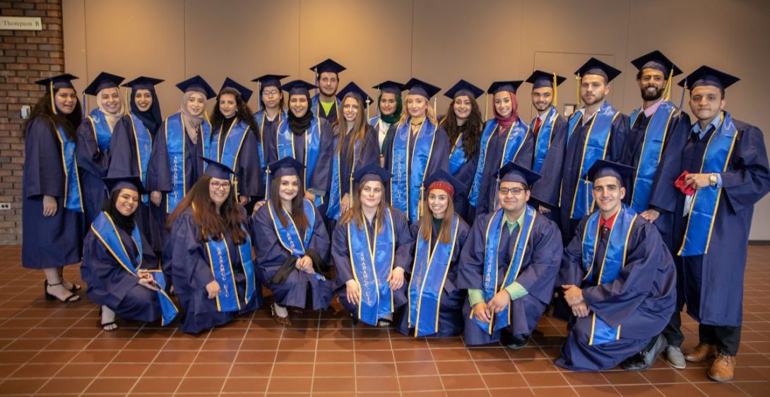 Graduating students in cap and gown pose for picture