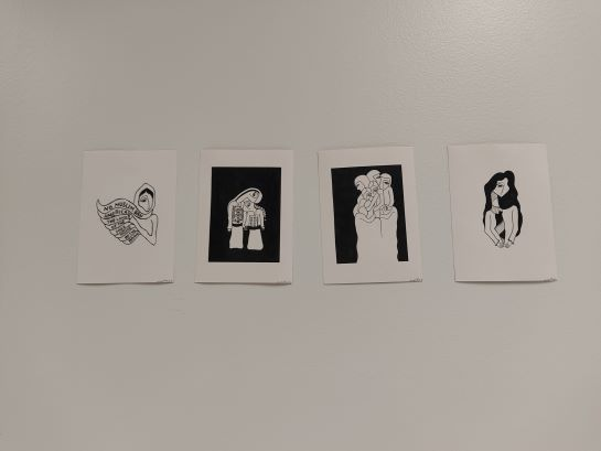 four prints hanging on the wall. each print is a white rectangle with drawings in black of women some of just torso with writing on their scarve and others with full body and embroidered clothing