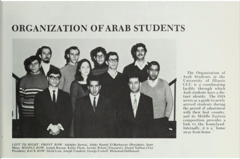 A Print out of a Newspaper article with a title on top over a black and white photograph of students standing in three rows, some are we wearing suits and ties, some seaters, some are wearing glasses, and some have mustaches. A short blurb describing the organization is to the right and a list of their names is under the photo